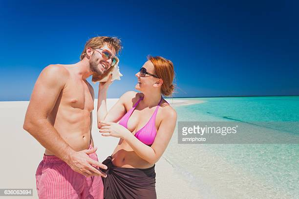 smiling couple sea shell calling tropical island beach