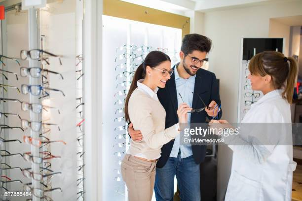 Smiling couple select eyeglasses in optical store