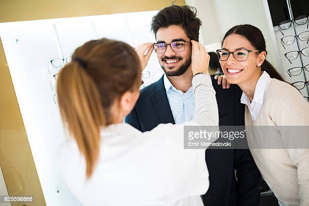 Smiling couple selecting eyeglasses in optical store