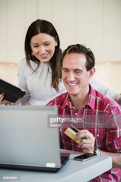 Smiling couple shopping online at home