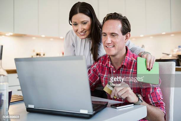 Smiling couple shopping online through credit card and laptop at home