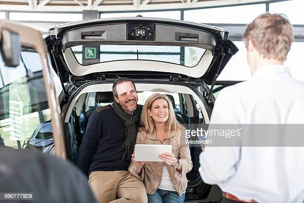 Smiling couple sitting in boot of new car at car dealership