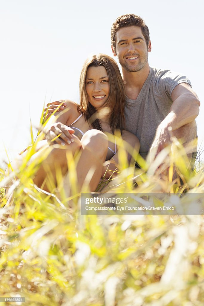 Smiling couple sitting in grass : Stock Photo