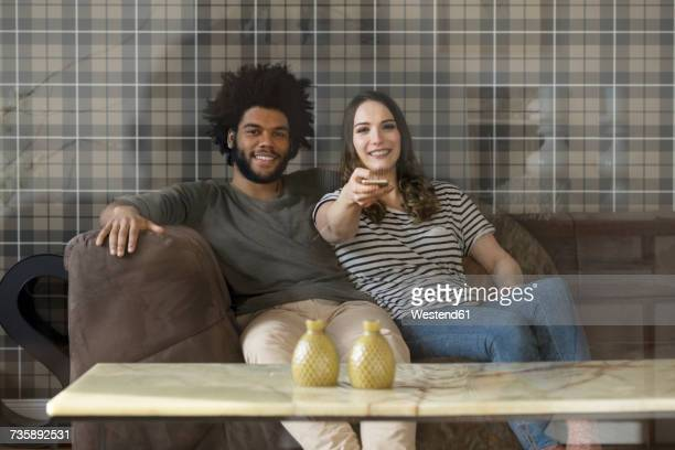 Smiling couple sitting on couch watching Tv