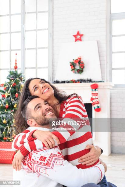 Smiling couple sitting on ground at home and embracing