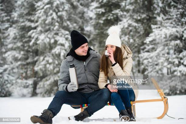 Smiling couple sitting on sled and drinking tea