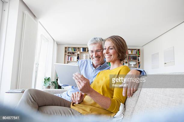 Smiling couple sitting on the couch at home using digital tablet