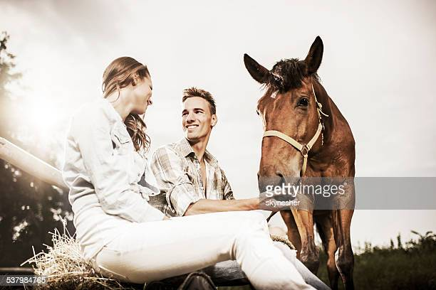 Smiling couple sitting with horse.