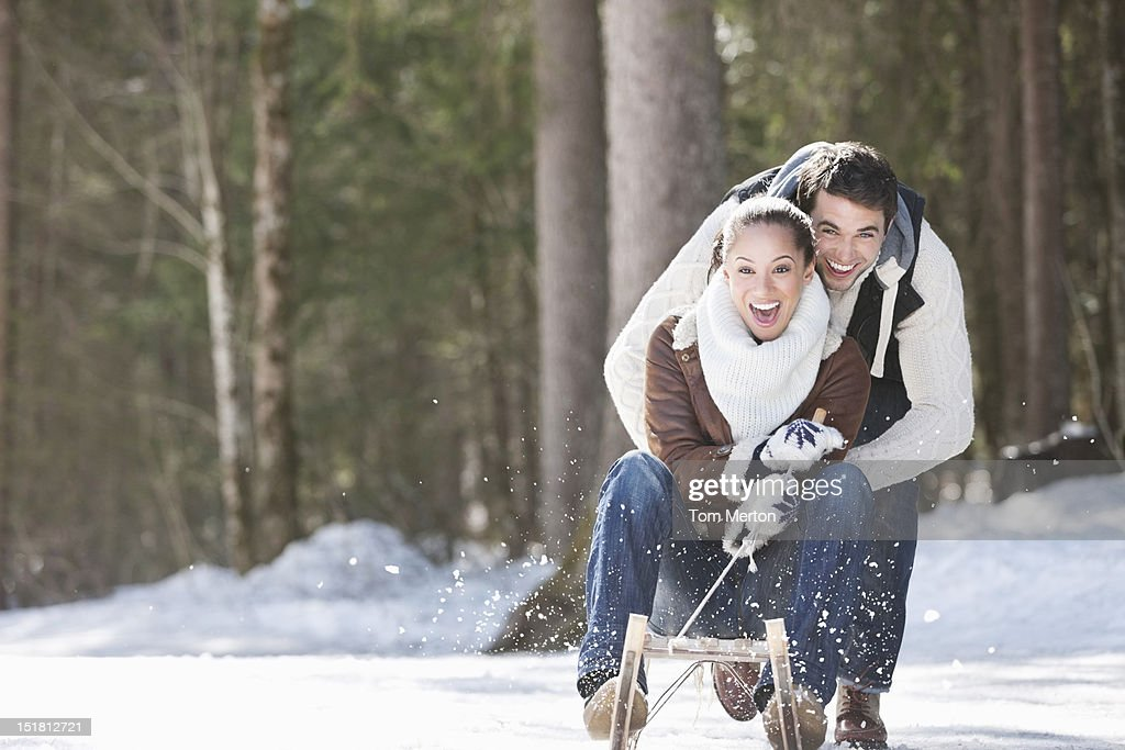 Smiling couple sledding in snowy field : Stock Photo