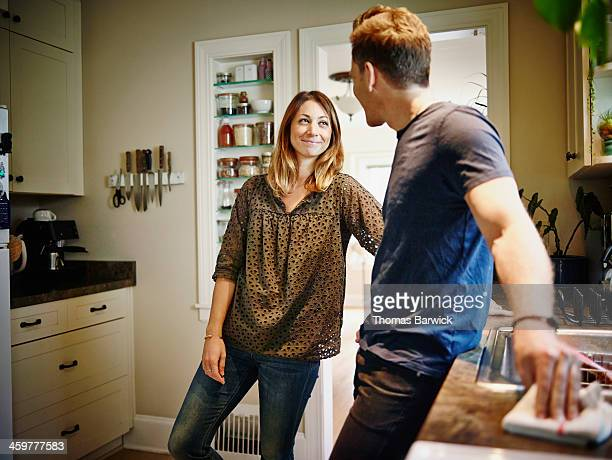Smiling couple standing at kitchen sink in home