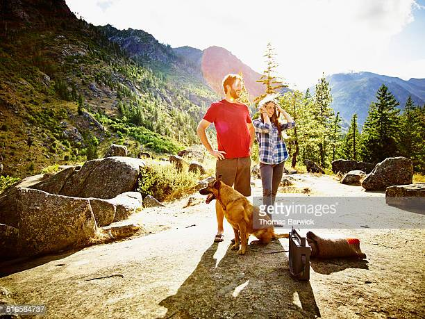 Smiling couple standing at overlook with dog