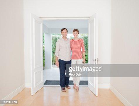 Smiling couple standing in doorway