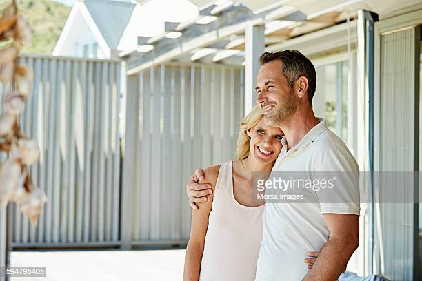 Smiling couple standing on patio