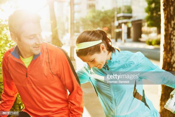 Smiling couple stretching together before early morning run on city street