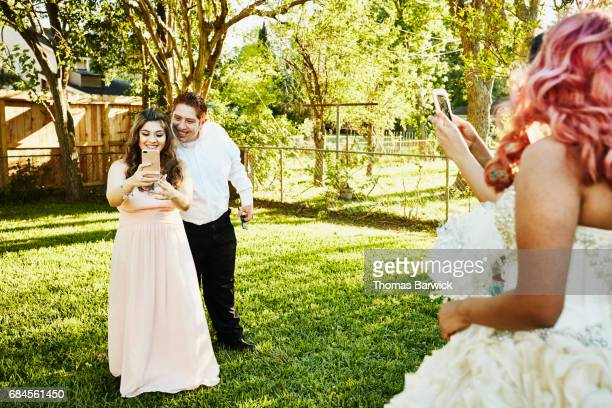 Smiling couple taking photo of cousin in quinceanera gown in backyard on summer evening