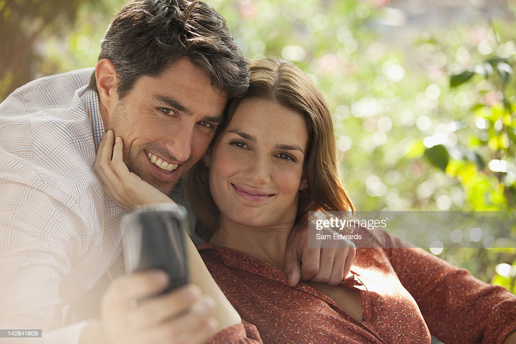 Smiling couple taking picture of themselves : Stock Photo