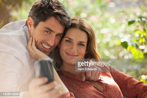 Smiling couple taking picture of themselves : Photo
