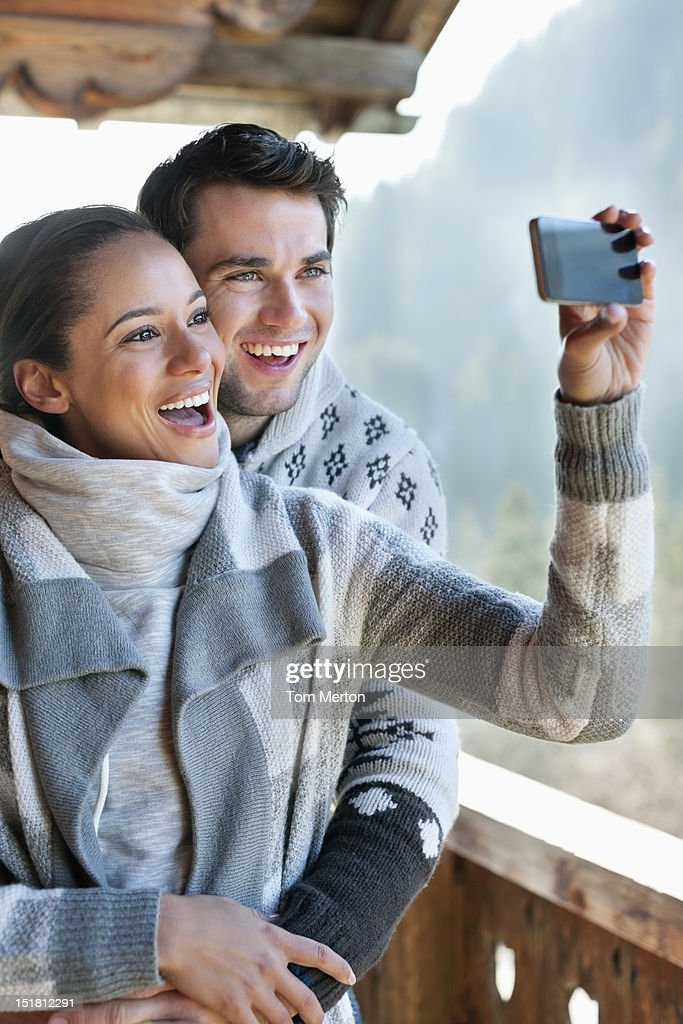 Smiling couple taking self-portrait with camera phone on cabin porch : Stock Photo