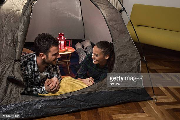 Smiling couple talking to each other during camping at home.