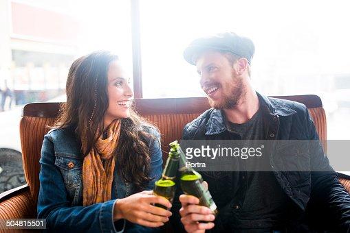 Smiling couple toasting beer bottles in restaurant