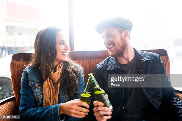 Smiling couple toasting beer bottles in restaurant