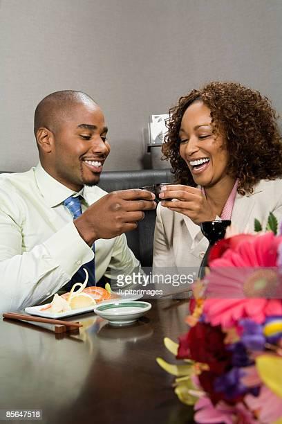 Smiling couple toasting with sake