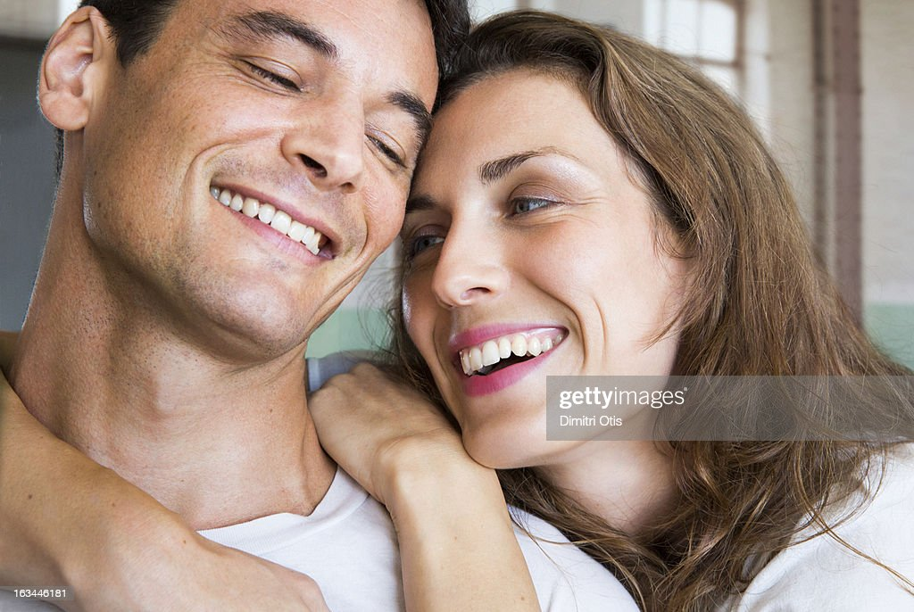 Smiling couple touching heads romantically