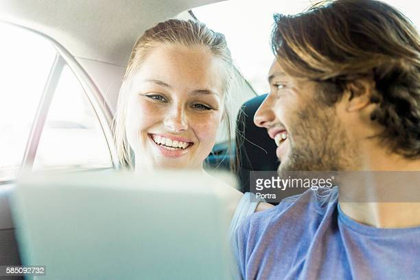 Smiling couple traveling in car on sunny day