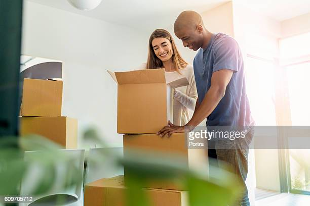 Smiling couple unpacking boxes in new house