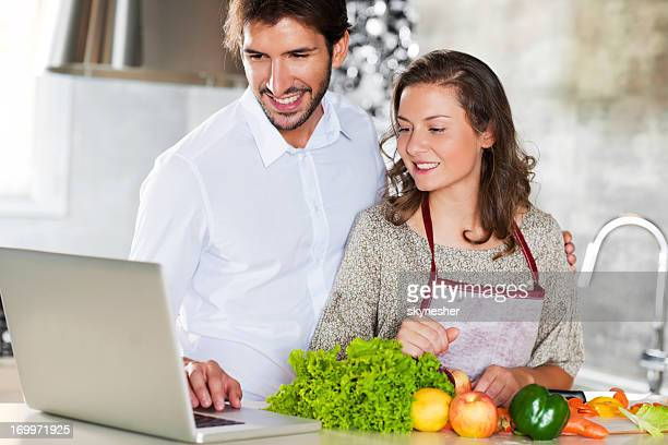 Smiling couple using a laptop in search for recipe.