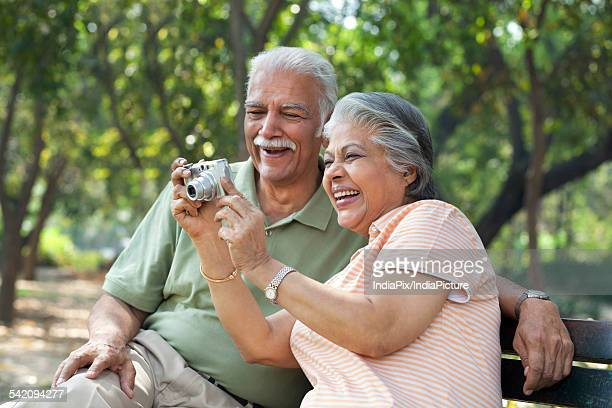 Smiling couple using digital camera at park