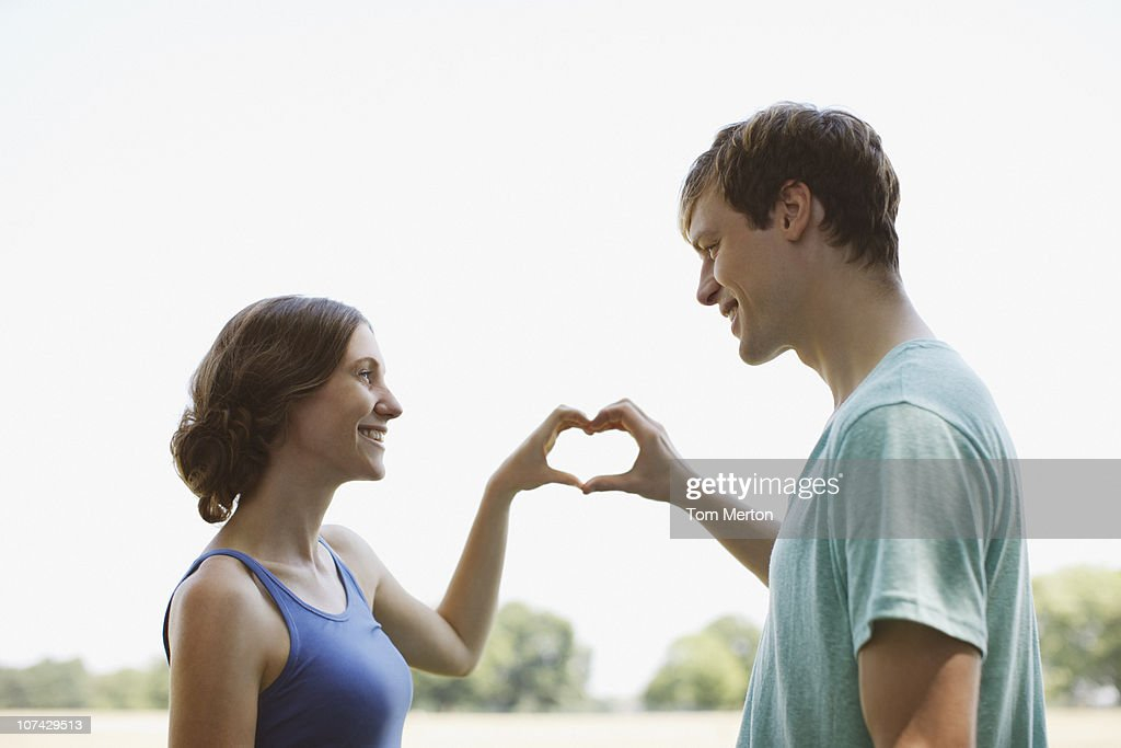 Smiling couple using hands to make heart shape : Stock Photo
