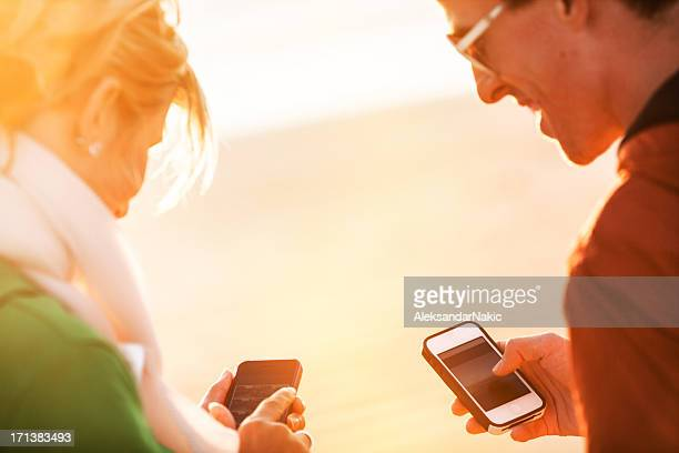 Smiling couple using smartphones