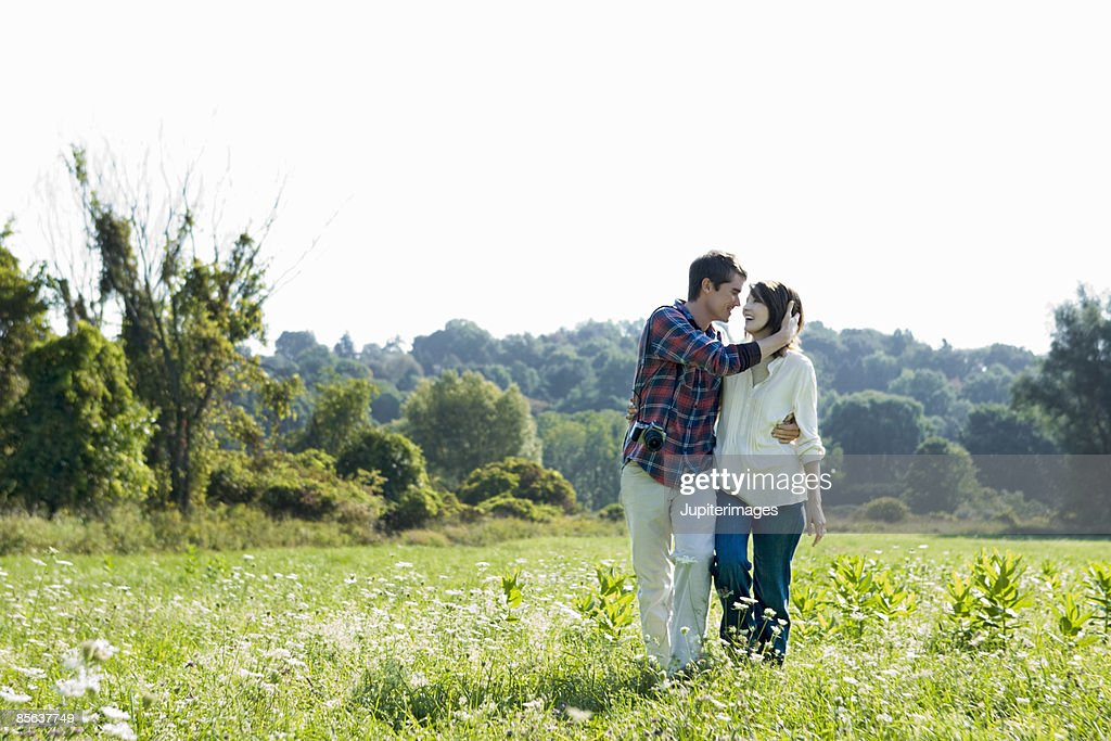 Smiling couple walking in field : Stock Photo