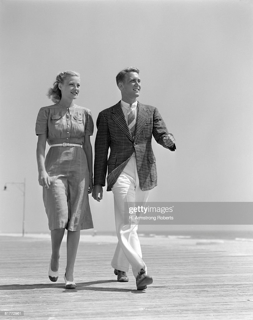 Smiling Couple Walking On The Beach She Is Wearing A Shirt Front Dress With A White Belt & Spectator Pumps He'S Wearing A Shirt Tie Sport Jacket & Pants.