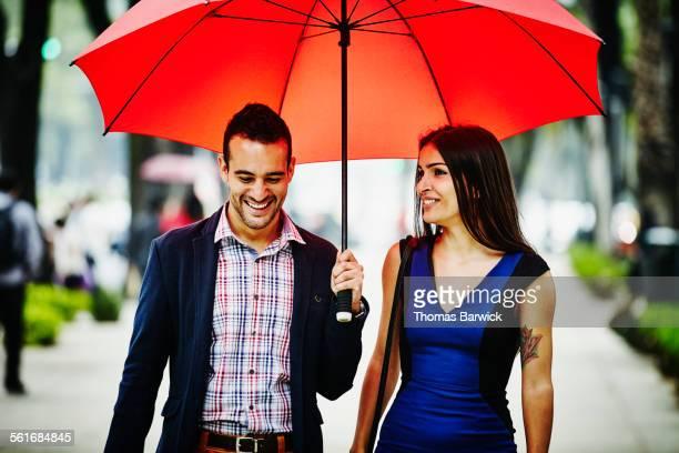 Smiling couple walking under umbrella