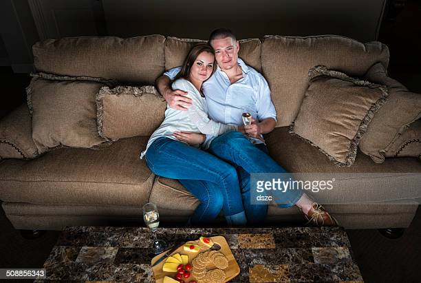 Smiling couple watches TV romance sitting on sofa with wine