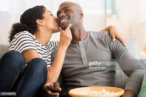 Smiling couple watching television on sofa