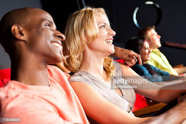 Smiling couple watching theater performance together