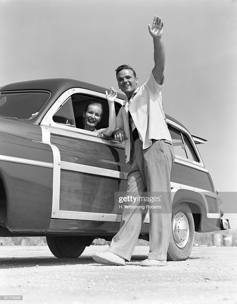 Smiling Couple Waving From A 1949 Mercury Station Wagon With Wood Paneled Body The Woman Is In The Drivers Seat The Man Is Standing Outside Sporty. : Stock Photo