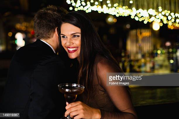 Smiling couple whispering at bar