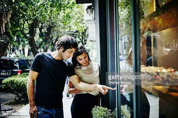 Smiling couple window shopping in city