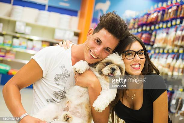 Smiling Couple with Dog in a Pet Shop