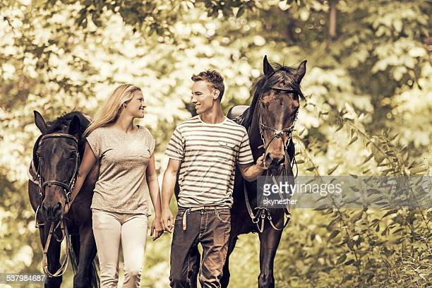 Smiling couple with horses.