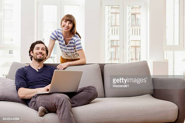 Smiling couple with laptop at home