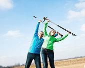 Smiling couple with nordic walking sticks warming up