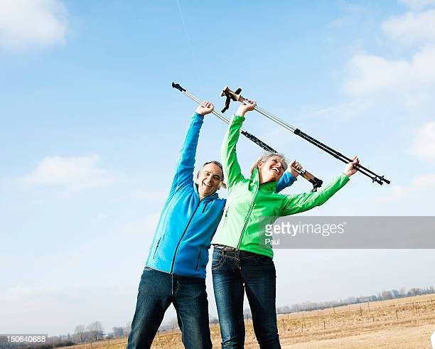 Smiling couple with nordic walking sticks warming up