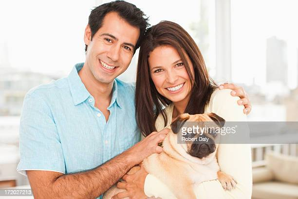 Smiling couple with pug