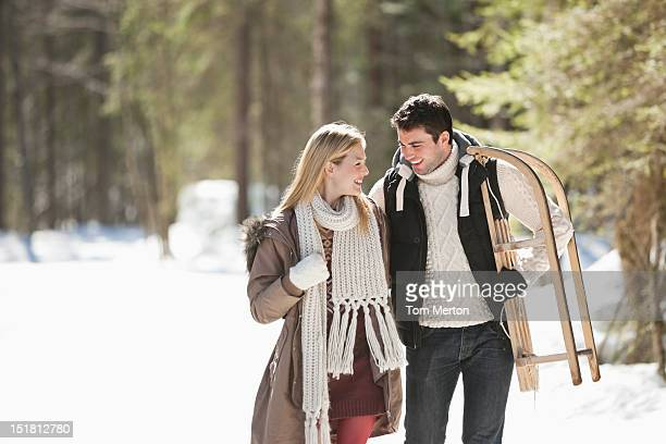 Smiling couple with sled walking in snowy woods