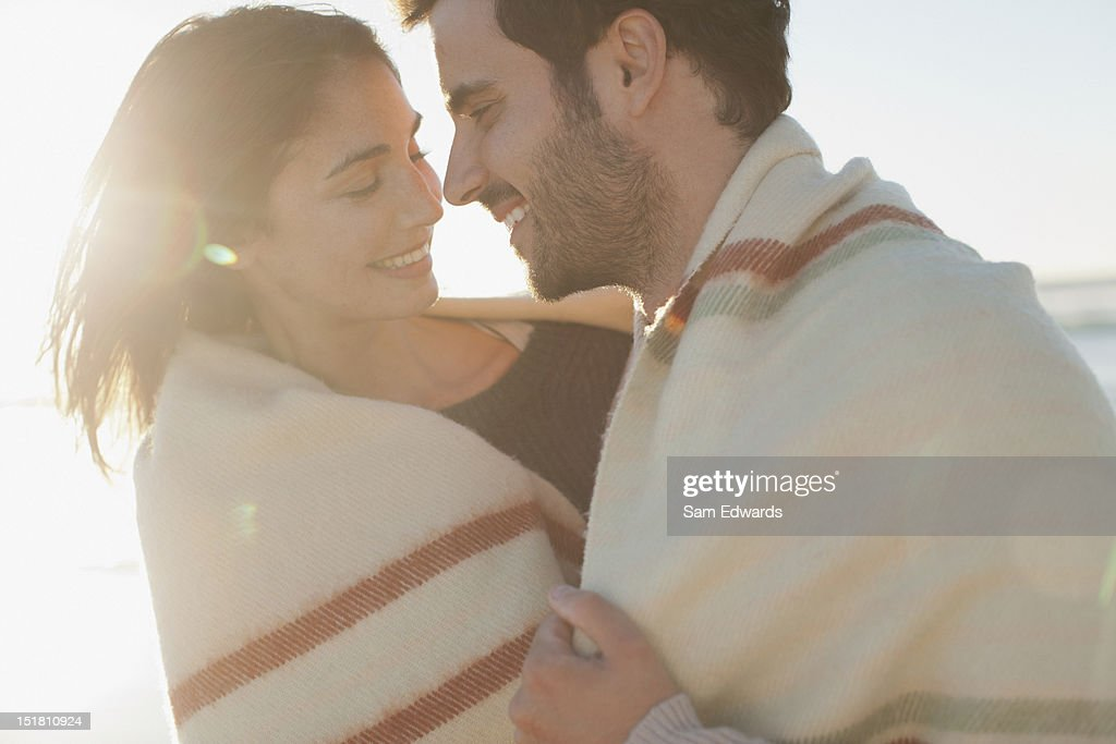 Smiling couple wrapped in blanket and hugging on beach : Stock Photo
